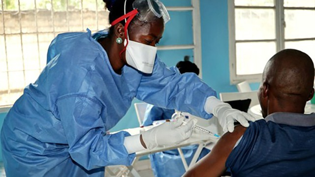 A health worker from the World Health Organization gives an Ebola vaccination to a front-line aid worker, Mbandaka, Congo