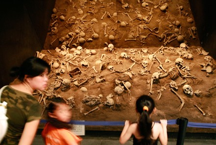 Visitors look at the skeletons of Chinese prisoners which were buried alive by Japanese soldiers. Photo by AFP.